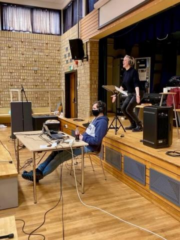 Fredag 12. februar var det korinnspeling i festsalen på Volda vgs. Siv Aurdal dirigerer med kjent engasjement, medan Anders Boska har kontroll over innspelinga. Foto: Hildur Sandstad Dalen.