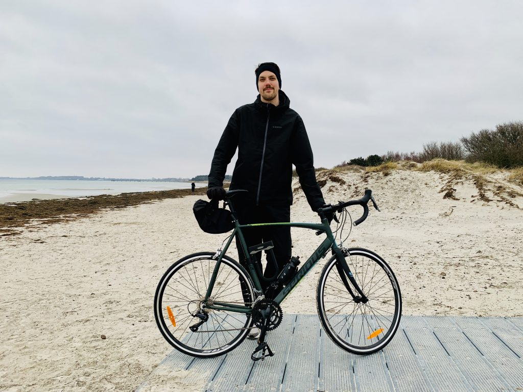 Bild på Andreas Palmblad med racingcykel på Lomma strand.