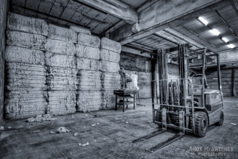 Black and white photo of a fork-lift truck with bags of cotton in a closed cotton UCO factory in Brugge, Belgium.