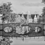 Black and white photo of a bridge over the canal with reflections and gable houses in Brugge, Belgium