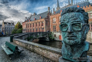 Statue of Frank Van Acker with surrounding canal, bench and historical buildings in Brugge, Belgium