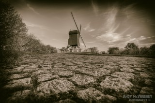Black and white landscape of the cobblestone path leading to the windmill in Brugge, Belgium