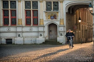 Morning cyclist in front of the Civil Registry on the Burg square in Brugge, Belgium