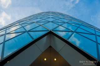 Detail photo of the London Gherkin with symmetrical lines, blue glass and cloud reflections in London, United Kingdom