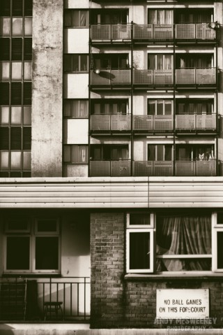 """Black and white photo of an apartment building with sign saying """"No Ball Games in This Forecourt"""" in Lodon, United Kingdom"""