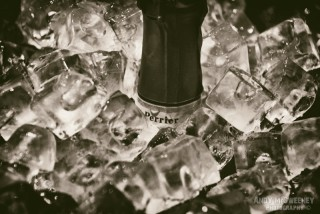 Close-up of a champagne Perrier bottle in ice cubes in London, United Kingdom