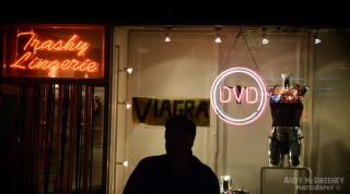 Man standing in front of a shop in Soho advertising trashy lingerie, dvd and viagra in London, United Kingdom