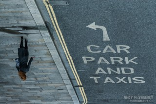 Woman walks the street next to street direction sign for car park and taxis in London, United Kingdom