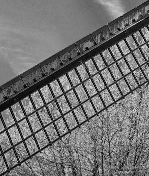 Black and white detail of the windmill blade with trees covered in frost during winter in Brugge, Belgium