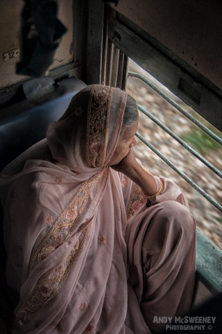 Portrait of an old Indian lady in sari looking out the window on a train in South-India