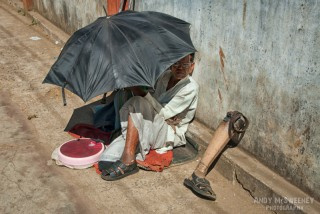 Portrait of a handicapped untouchable Indian man with false leg and scale hiding under umbrella on the streets of South-India