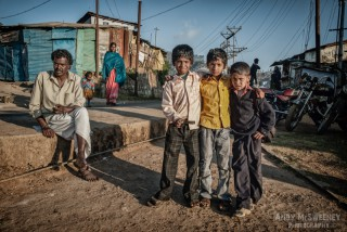 Colorful portrait of an Indian guide and his cool little followers in the slums of South-India