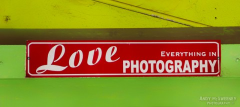 """Colorful street advertising sign saying """"Love Everything in Photography"""" in Margao, India"""