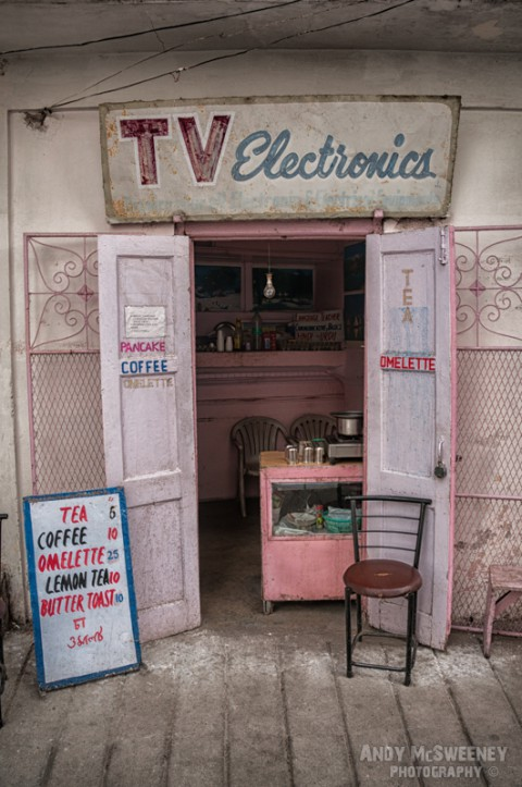 """Colorful shop with old advertising sign offering """"TV Electronics"""" and drinks and snacks in India"""