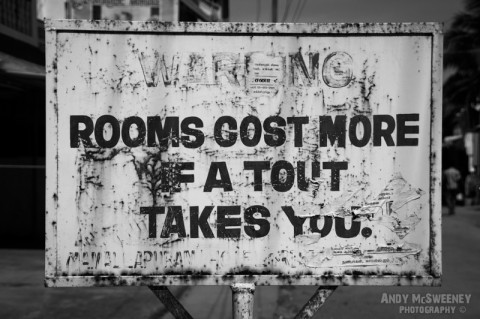 """Old black and white street sign in Mamalapuram India warning """"Rooms Cost More if A Tout Takes You"""""""
