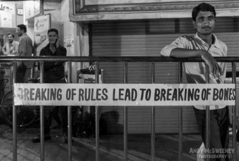 """Black and white street banner saying """"Breaking of Rules Leads to Breaking of Bones"""" with surrounding people in India"""