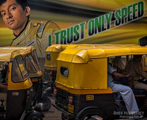 Bollywood street poster saying 'I Trust Only Speed' with surrounding riksja's and their drivers.