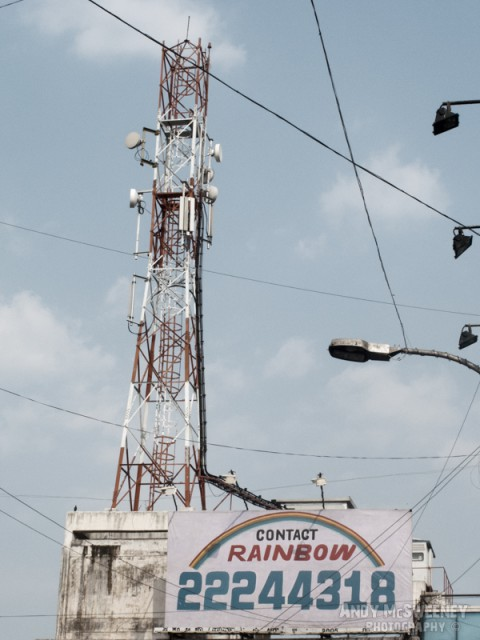 """Street sign in India saying """"Contact Rainbow"""" with street lamps and tower."""