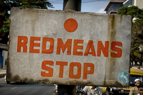 """Street sign in India saying """"Red Means Stop""""."""