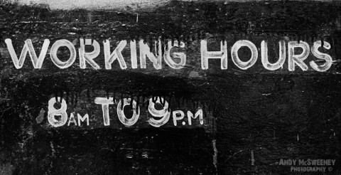 """Black and white street sign in India saying """"Working Hours 8am to 9pm"""""""