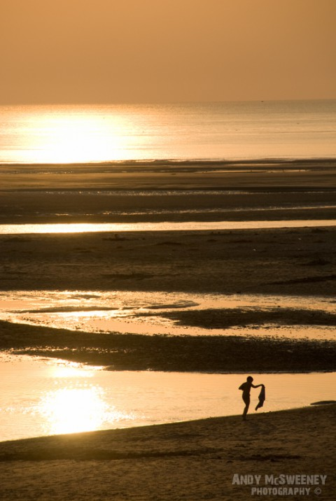 Boy walking the beach at sunset in Zeeland, The Netherlands