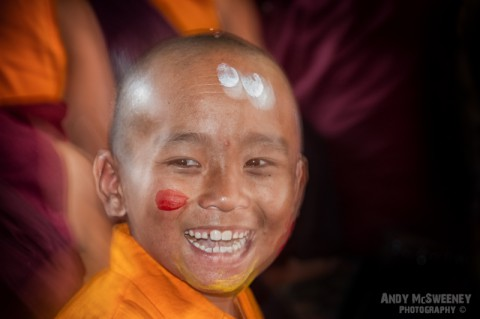Colorful portrait of a little monk during puja ceremony in the monastery of Bylakuppe, South-India