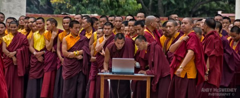 Colorful portrait of monks during celebrations, with focus on the monk with computer in the monastery of Bylakuppe, South-India