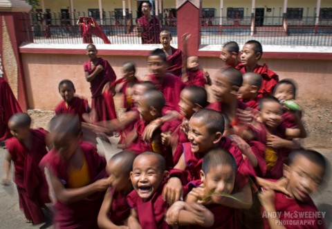 Colorful portrait of little monks trying to get in front of the camera in the monastery of Sera, South-India