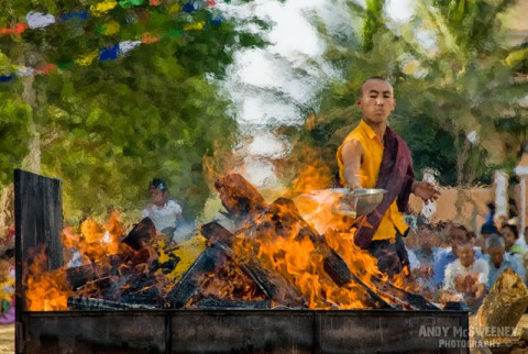 Colorful portrait of a monk doing a fire offering at a puja ceremony in the monastery of Bylakuppe, South-India
