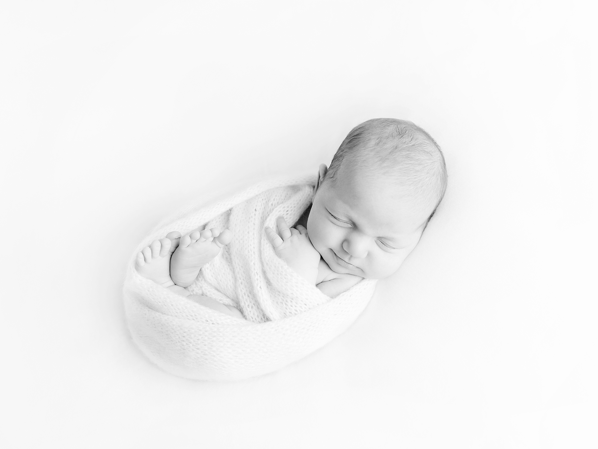 wrapped up baby in black and white on back newborn photography edinburgh midlothian