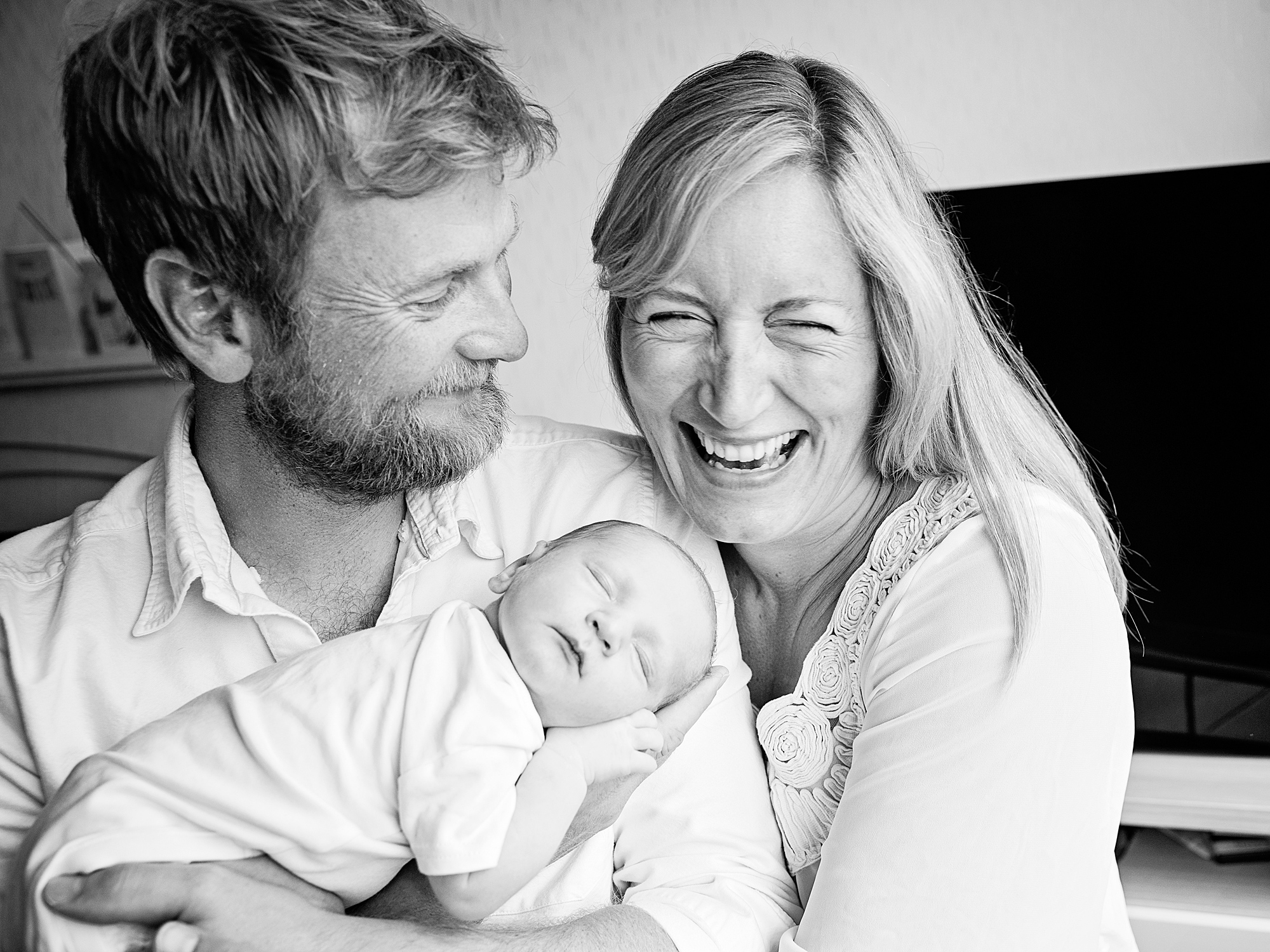 mum and dad laughing at home newborn family photography in edinburgh midlothian