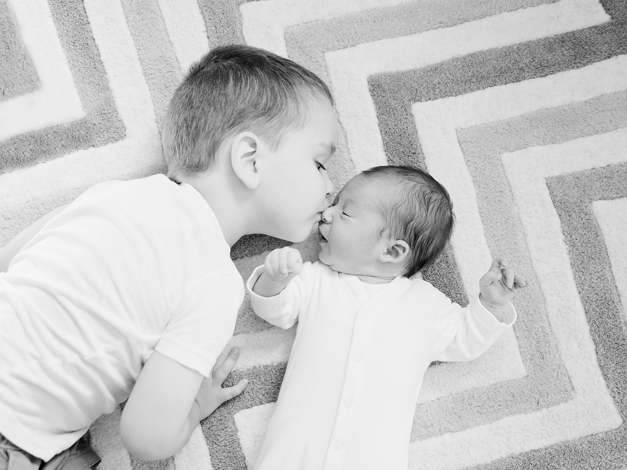 toddler brother kissing newborn at home family photography in edinburgh midlothian