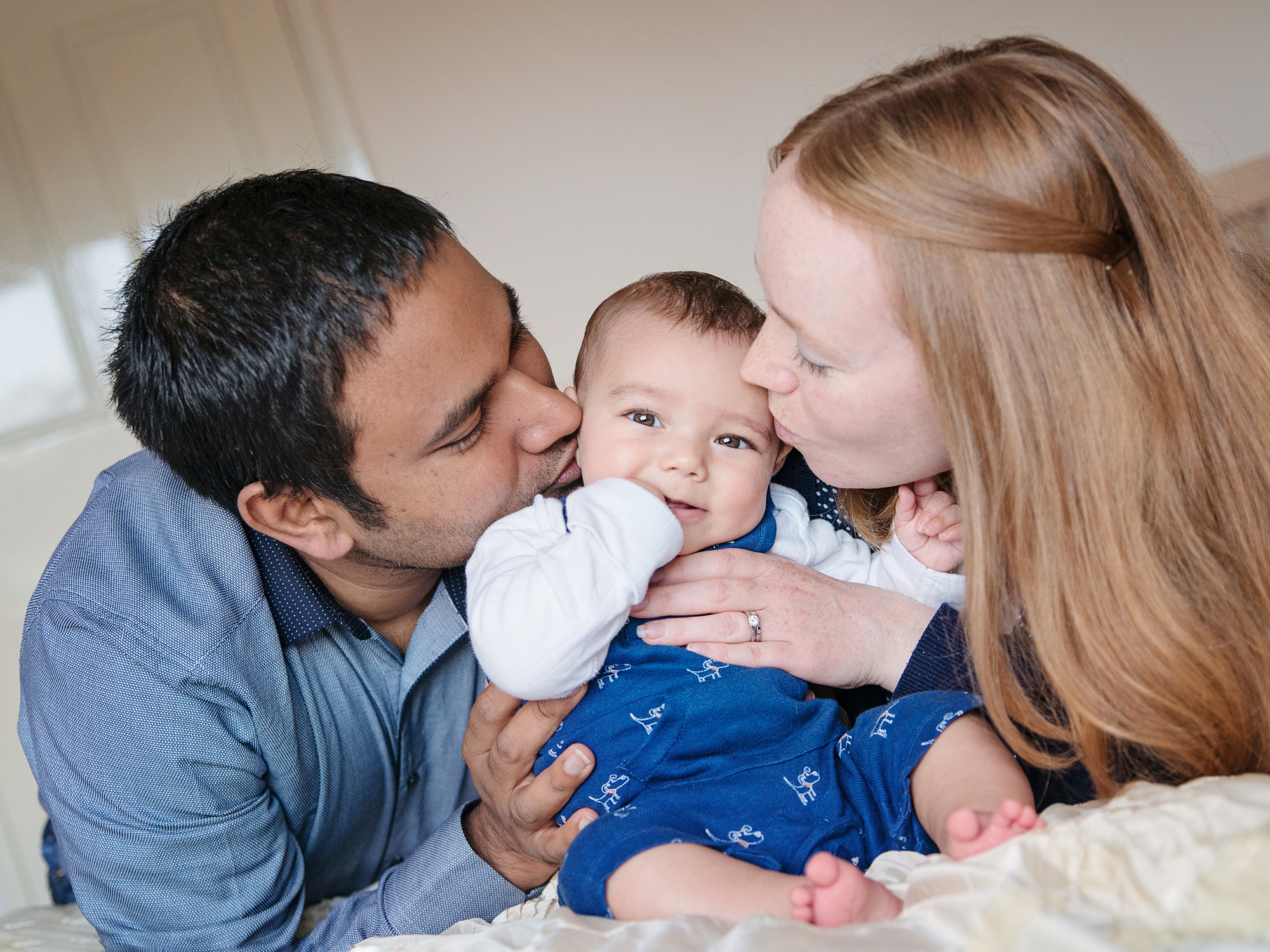 mum and dad kissing baby at home family photography in edinburgh midlothian
