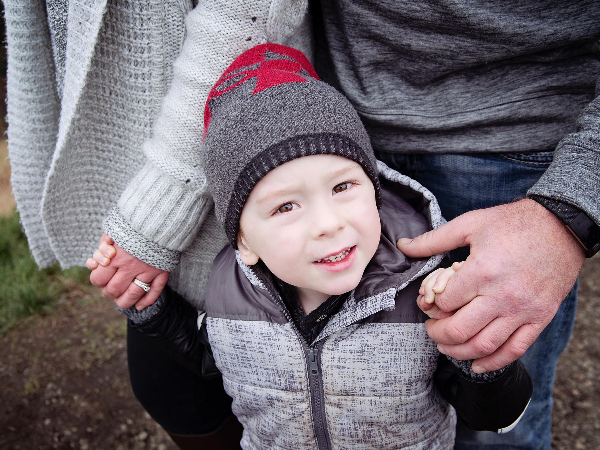 boy holding parents hands lifestyle outdoor family photography in edinburgh midlothian