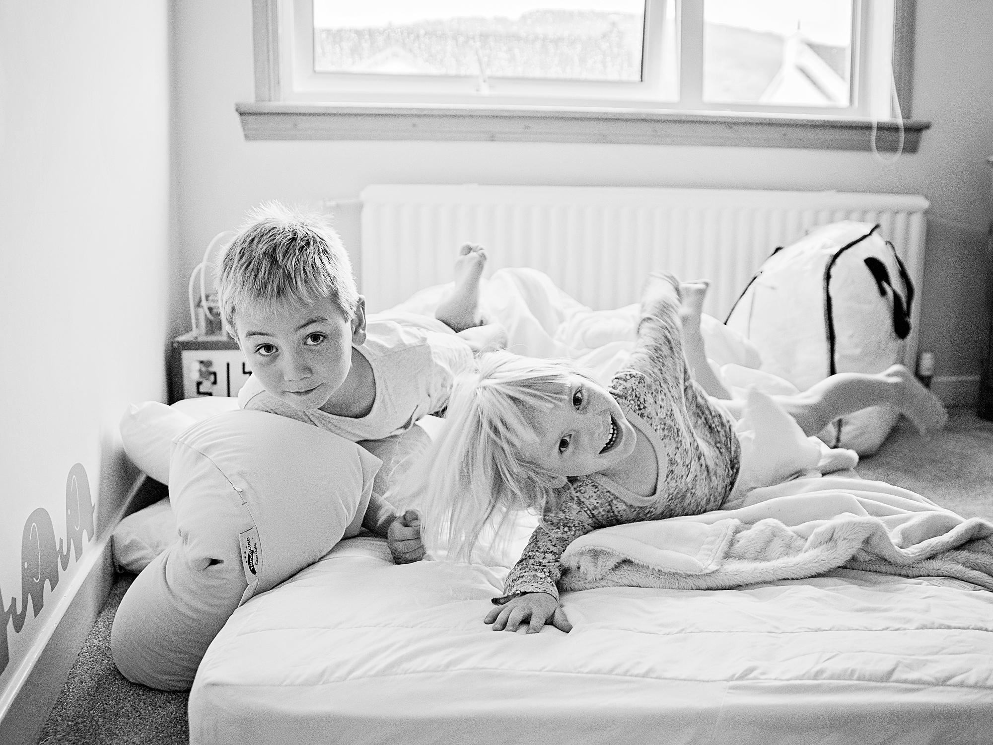 brother and sister playing on the bed at home lifestyle family photography in edinburgh midlothian
