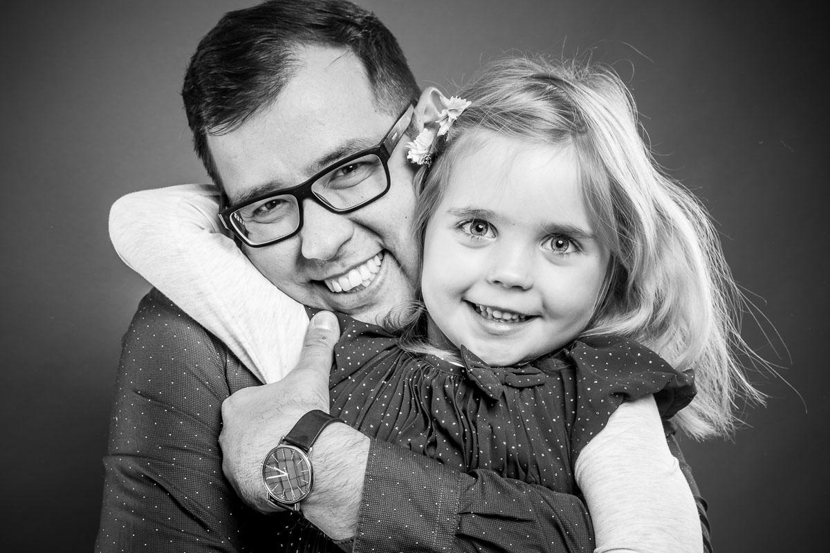 Tochter-umarmt-Vater-lachend-Fotostudio-blendenspiel