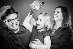 Familie-lacht-Spaß-mit-Hüten-Fotostudio-blendenspiel