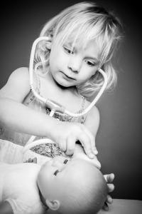 Mädchen spielt Arzt mit Puppe