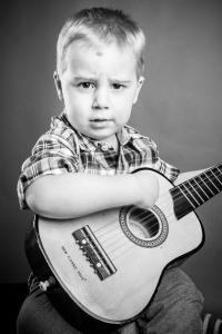 kleiner Junge singt hingebungsvoll zur Gitarre