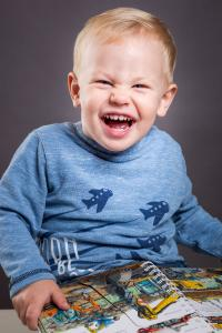kleiner Junge lacht frech über Buch