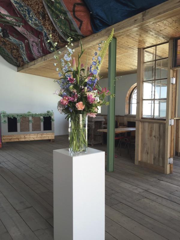 Een boeket in een vaas op een zuil bij een evenementen-locatie
