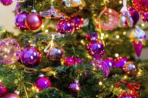 Gedecoreerde kerstboom met roze kerstballen.