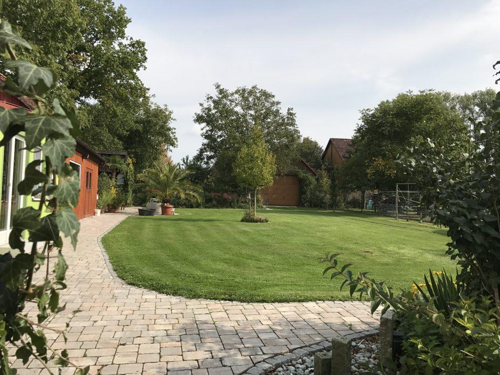 Blick von der Hausterrasse in den oberen Garten mit Hausbaum