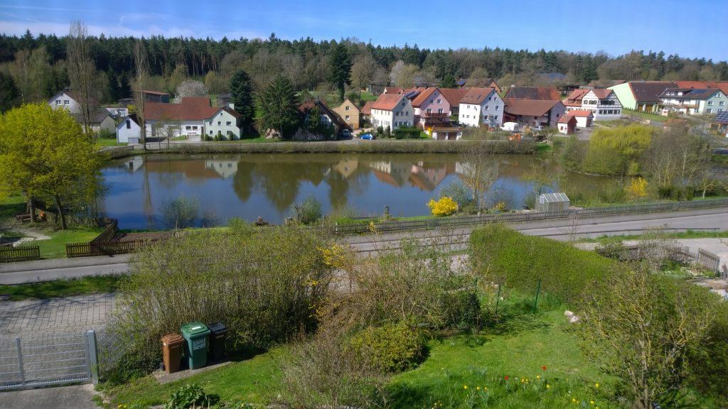 Blick auf den Dorfweiher und die Gartenparzellen