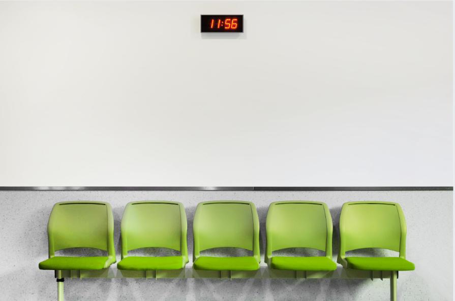 Viisi tyhjää vihreää seinään kiinnitettyä penkkiä. Valkoisella seinällä mustatauluinen digitaalinen kello, jossa lukee 11.56.