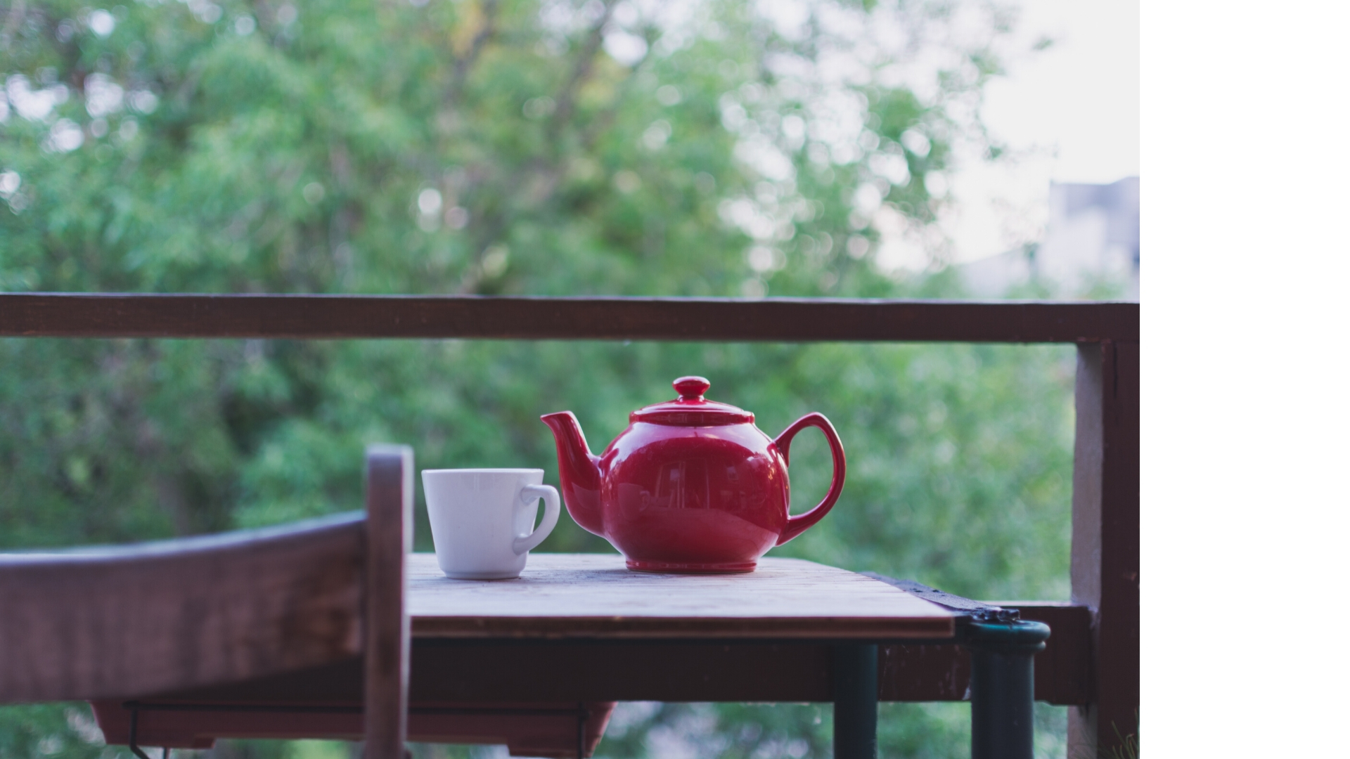 A red teapot and a white cup are on a wooden balcony table. Wooden chair's back is visible. Over the balcony bar there is dark green leaves of a tree.