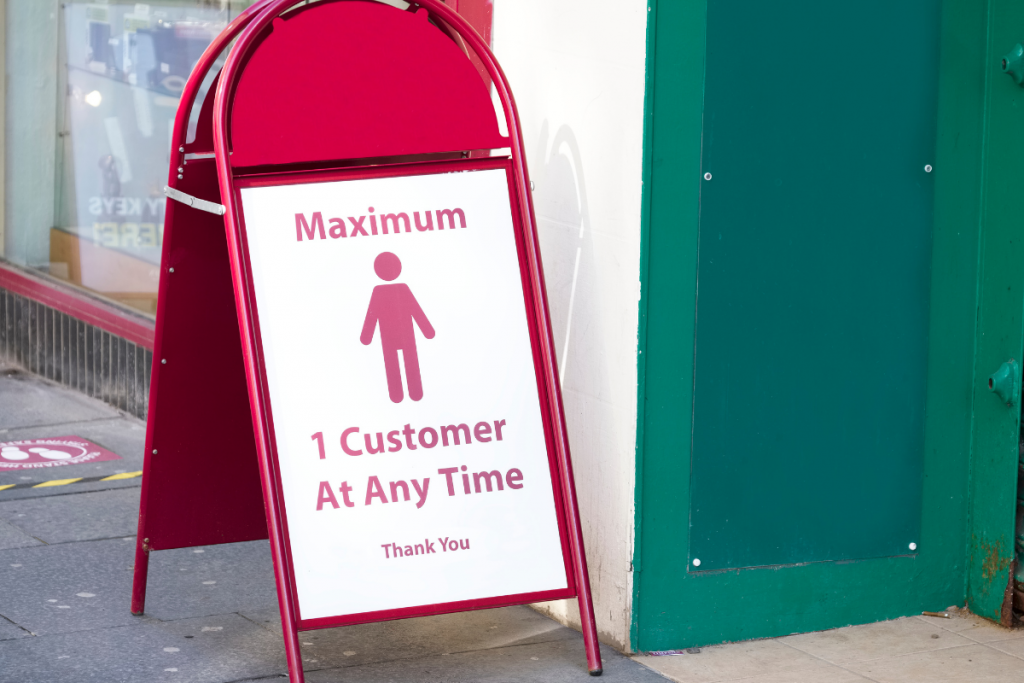 Kuvassa on kylttistandi liikkeen ulkopuolella, jossa on kuvake ihmisestä, jonka alla on teksti englanniksi yhden asiakkaan maksimimäärästä liikkeessä.