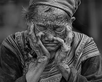 Svartvit bild med gammal kvinna som sitter med händerna vid kinderna och slutna ögon, kaffe kan påverka sömnen