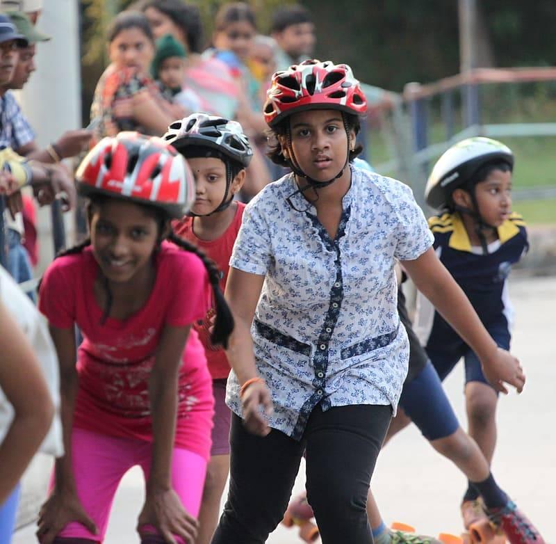 Barn med hjälmar åker rullskridskor och rollerblades. Rekommendationer för fysisk aktivitet för barn och ungdomar är en timmas rörelse per dag