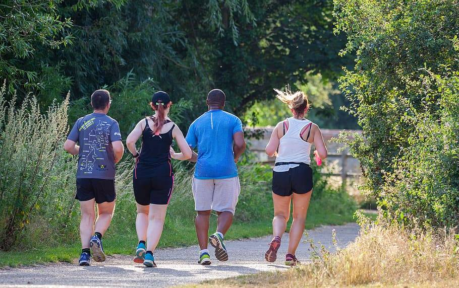 Fyra personer, två män och två kvinnor joggar tillsammans i naturen med linne och shorts en solig varm dag